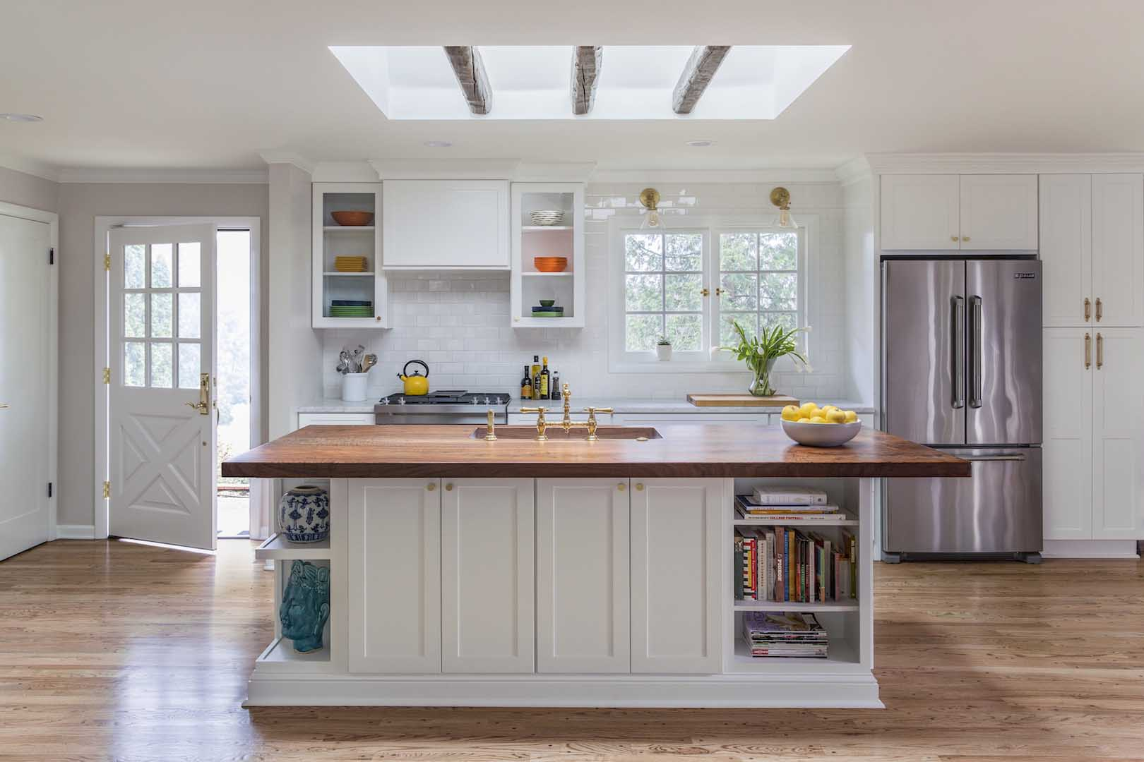 Full kitchen with open shelving, island, and skylight with rustic beams