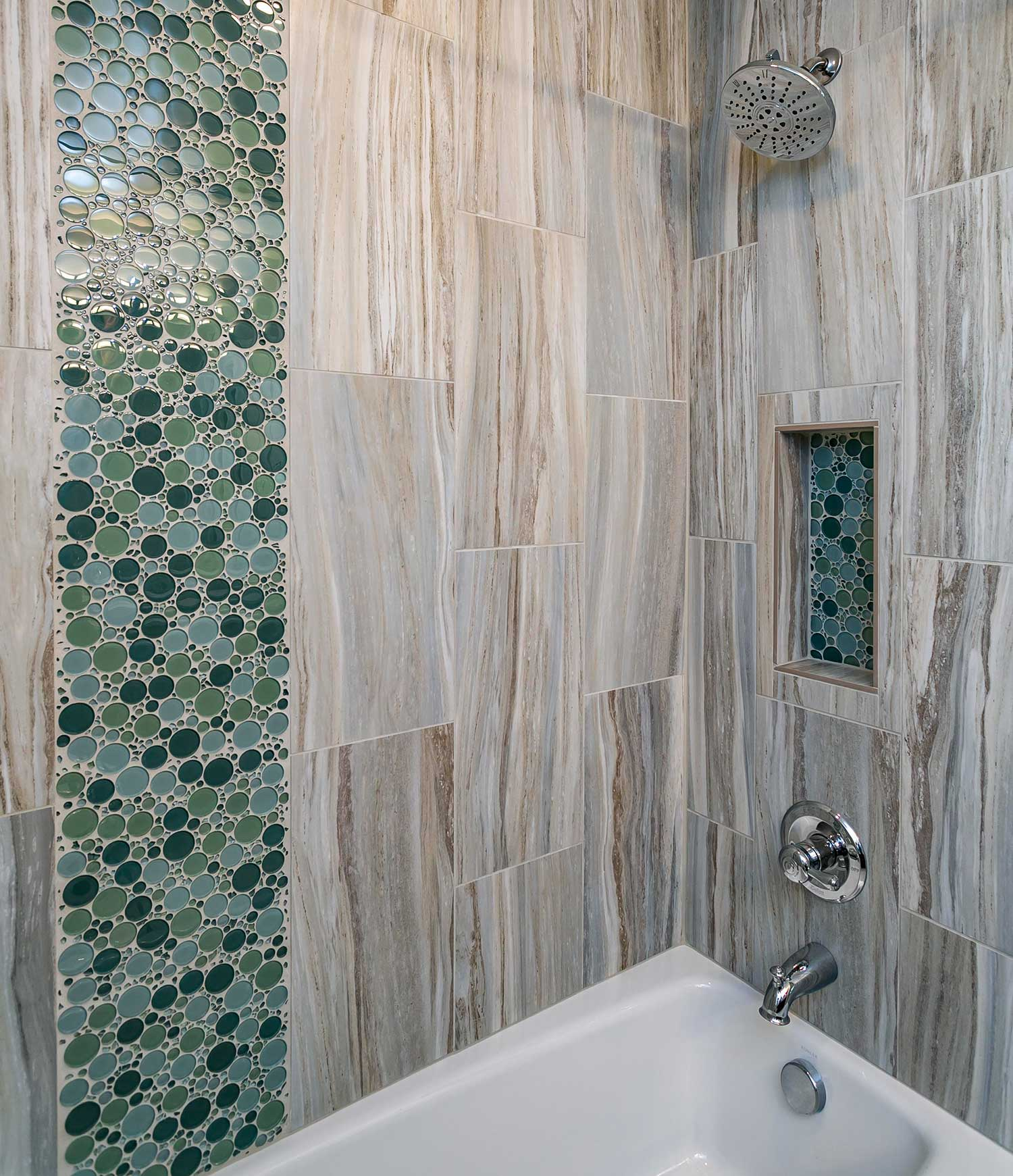 Shower and tub combination with teal tile that give the appearance of bubbles