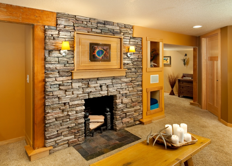 Contemporary basement remodel with natural rock fireplace