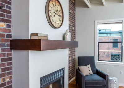 Finished-Brick-Walls-Framed-in-Gas-Fireplace-Dark-Wood-Shelf