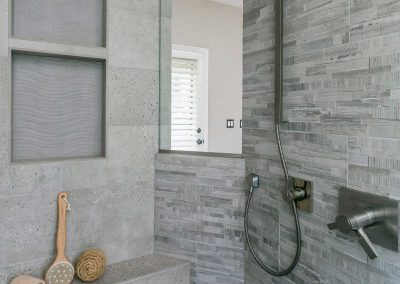 Master walk in shower remodel with window, grey tile, and green pebble shower floor