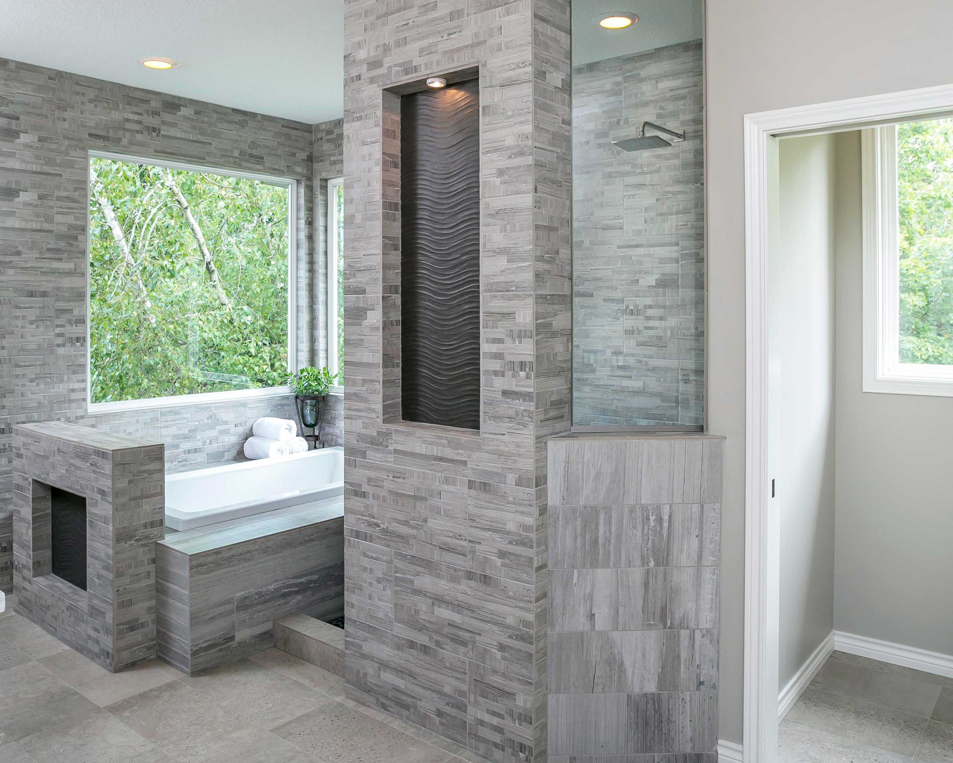 Grey tiled walk in shower and bathtub