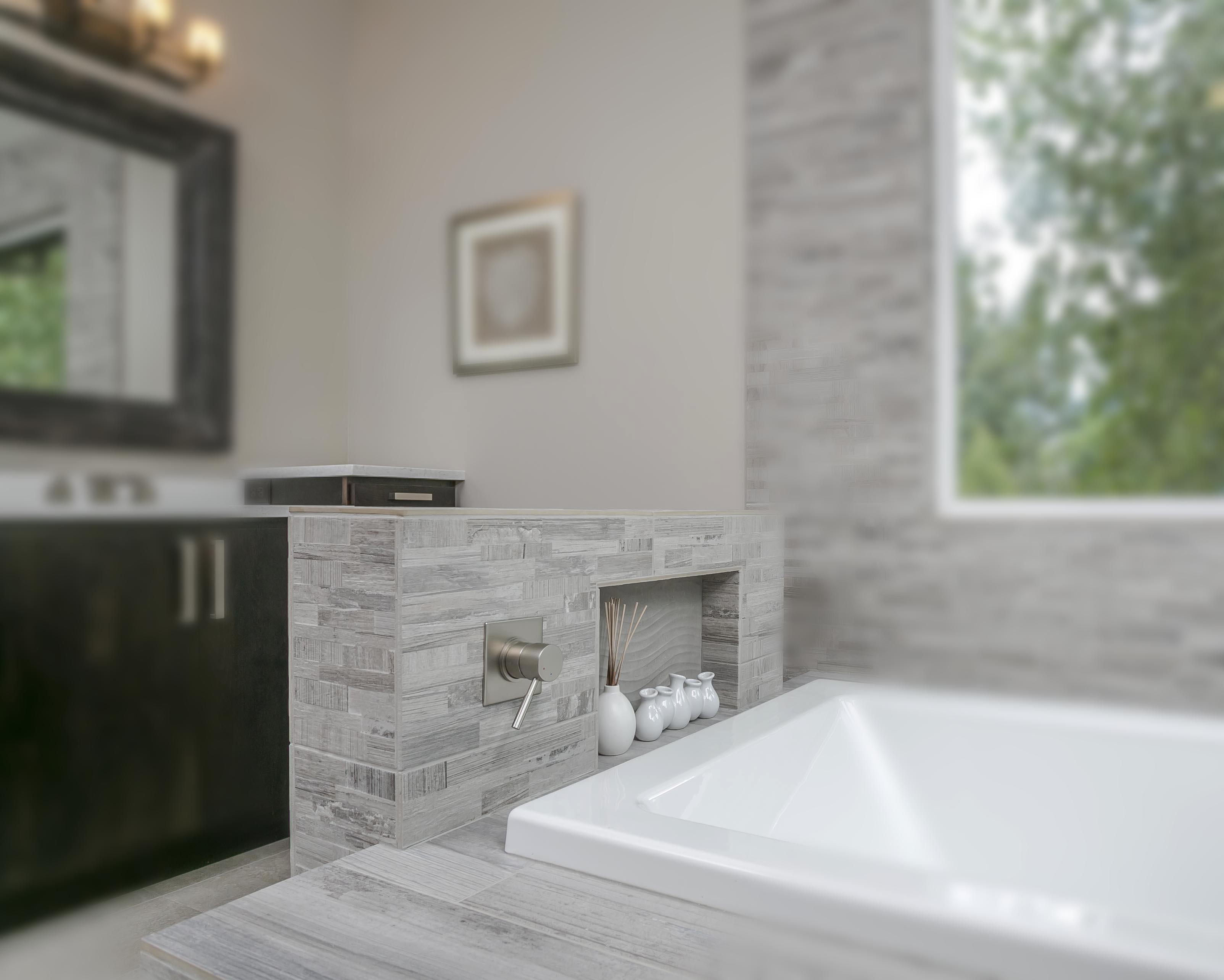 Built in bathtub with grey tiles next to a window