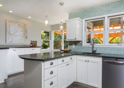 Modern-Kitchen-with-Bubble-Glass-Pendant-Lights-Herringbone-Accent-tile-Counter-to-Ceiling-Teal-Subway-Tile-Backsplash-Black-Counters-Side-Bar-White-Cabinets