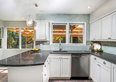 Modern-Kitchen-with-Bubble-Glass-Pendant-Lights-Herringbone-Accent-tile-Counter-to-Ceiling-Teal-Subway-Tile-Backsplash-Black-Counters-Side-Bar-White-Cabinets-Peninsula