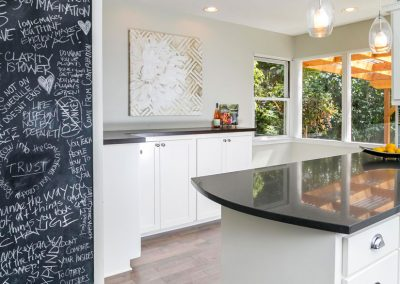 Modern-Kitchen-with-Bubble-Glass-Pendant-Lights-Herringbone-Accent-tile-Counter-to-Ceiling-Teal-Subway-Tile-Backsplash-Black-Counters-Side-Bar-White-Cabinets-Wall-Chalkboard
