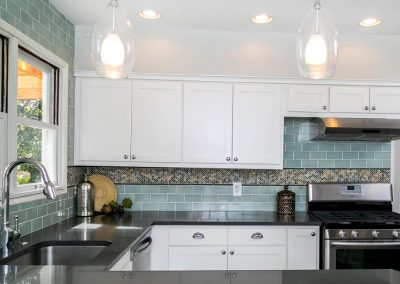 Modern-Kitchen-with-Stainless-Range-Bubble-Glass-Pendant-Lights-Herringbone-Accent-tile-Counter-to-Ceiling-Teal-Subway-Tile-Backsplash-Black-Counters-Side-Bar-White-Cabinets