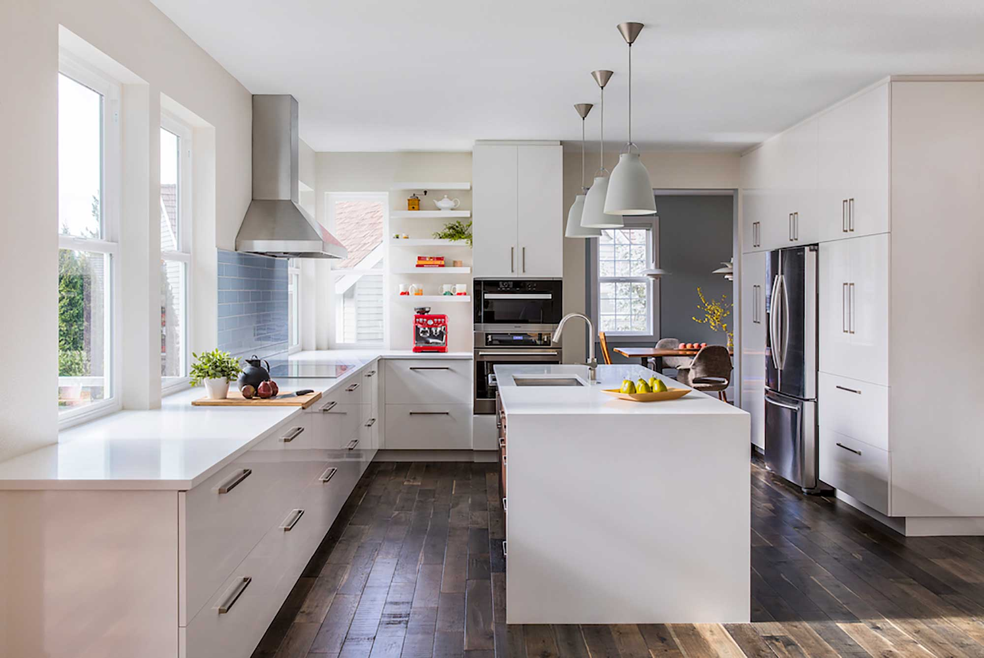 Kitchen remodel with white cabinets, countertops, and a seamless waterfall island