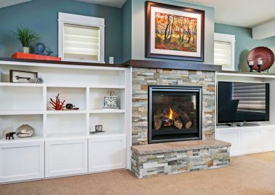 Stacked-Stone-Fireplace-Surround-with-Custom-Dark-Wood-Mantel-and-Built-in-Shelving