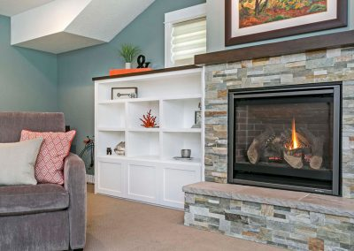 Stacked-Stone-Fireplace-Surround-with-Custom-Dark-Wood-Mantel-and-Stone-Hearth-Built-in-Shelving