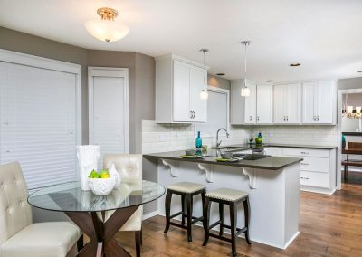 Traditional-Kitchen-with-White-Shaker-Cabinets-Subway-Tile-Backsplash-Stainless-Steel-Appliances-and-Natural-Wood-Floors