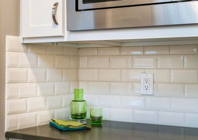 Transitional-Kitchen-With-Gloss-White-Subway-Tile-Backsplash-White-Cabinets-built-in-Microwave