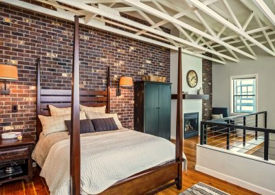 Transitional-Loft-Finished-Brick-Walls-Hardwood-Floors-Framed-in-Gas-Fireplace-Sconse-Bed-Lighting