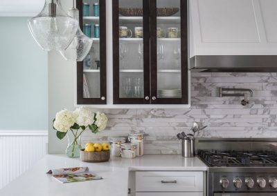 Two-Tone-Kitchen-Cabinets-with-Glass-Uppers-Built-in-Wrapped-Hood-Pot-Filler