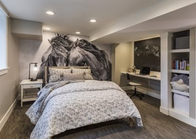 Basement bedroom with full wall accent picture mural built in shelving and study nook
