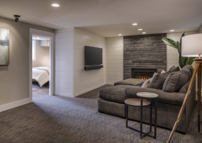 Basement family room with shiplap accent walls barnwood fireplace surround picture lighting