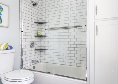 Kids bathroom with white subway tile corner shelves twilight tile floors