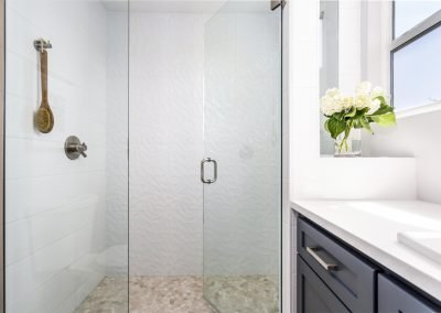 Master bath with shaker cabinets brushed nickel pulls quarts counter single panel shower door and shower window pebel shower floor textured tile shower walls