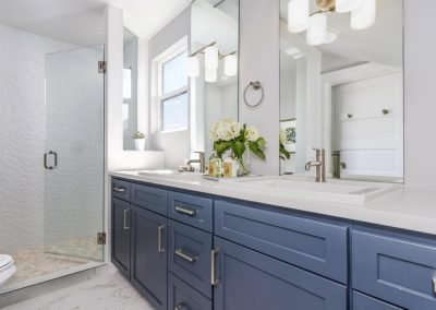 Master bath with shaker cabinets quarts counter single panel shower door and shower window peble shower floor textured tile shower walls top mount sinks counter to ceiling vanity mirrors